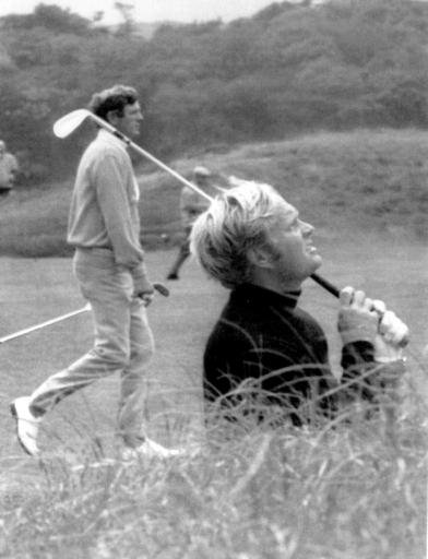 Jack Nicklaus follows the flight of the ball after hitting out of the bunker on the fifth fairway in the British Open play-off on July 12, 1970 at St. Andrews, Scotland. In background is his play-off opponent, Doug Sanders. Nicklaus captured the title by one stroke.