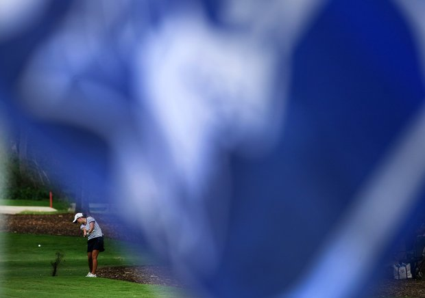 A Duke Blue Devil flag flies in the foreground as Lindy Duncan of Duke hits her shot at No. 18 during Round 1 of the Traditions Golf Club for the Women's Division I Golf Championships.
