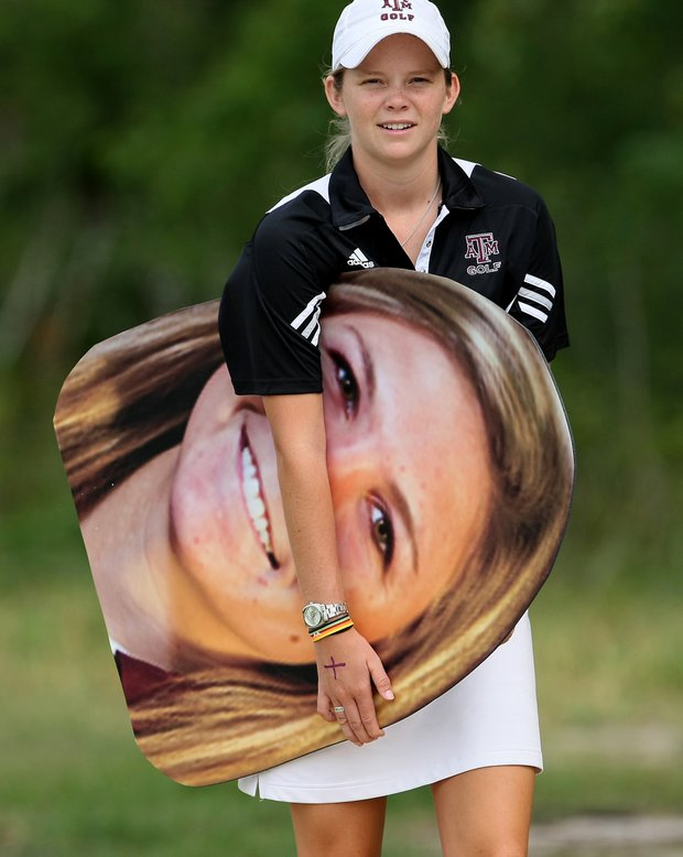 Janell Lysack of Texas A&M carries a huge cut-out of Susy Grunden  during Round 1 of the Traditions Golf Club for the Women's Division I Golf Championships.