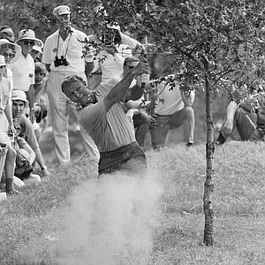 Arnold Palmer hits from behind some trees on the first hole during the third round of the PGA Championship and went on to par the hole at Southern Hills Country Club, Aug. 15, 1970, Tulsa, Okla.