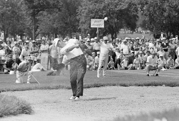 A marshal at the PGA Championship appears to be giving a slap at the ball with his sign as Dave Stockton of Westlake, Calif., blasts from a sand trap during the final round, Aug. 16, 1970. Stockton won the championship with a 1-under par 279 for the 54-hole play.