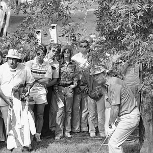 Arnold Palmer peers out from under a tree limb as he watches his shot on the seventh hole of the first round of the 61st PGA Championship in Birmingham, Mich., Aug. 3, 1979. Palmer carded an 81 on the round, putting him several strokes off the pace set by leader Tom Watson