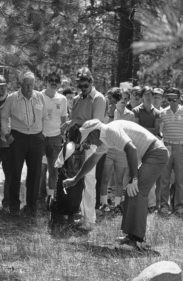 His tee shot into the woods, Arnold Palmer gently lifts a twig from his ball for a clear shot to the ninth fairway in first round action of the U.S. Senior Open Championship at Edgewood Tahoe golf course in Stateline, Nev., June 28, 1985. Palmer bogeyed the hole, but finished the day even at par 72.