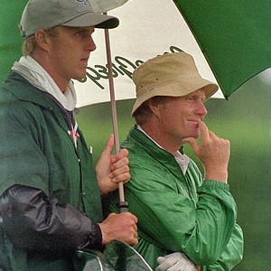 Golfer Jack Nicklaus waits his turn to putt as his son, Jackie, holds the umbrella on the third hole of the opening round at the U.S. Open Golf Championship in Southampton, N.Y., on Thursday, June 12, 1986.