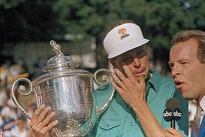 Bob Tway wipes tears from his eyes while holding the PGA Championship trophy on the 18th green of the Inverness Club in Toledo, Ohio, Aug. 11, 1986. Tway sank a birdie trap shot on the final hole to defeat Greg Norman.
