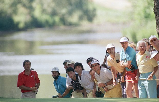 With the gallery looking on, Curtis Strange watches his shot from the water near the 3rd hole during final round of the U.S. Open in Brookline, Mass., Sunday, June 19, 1988.