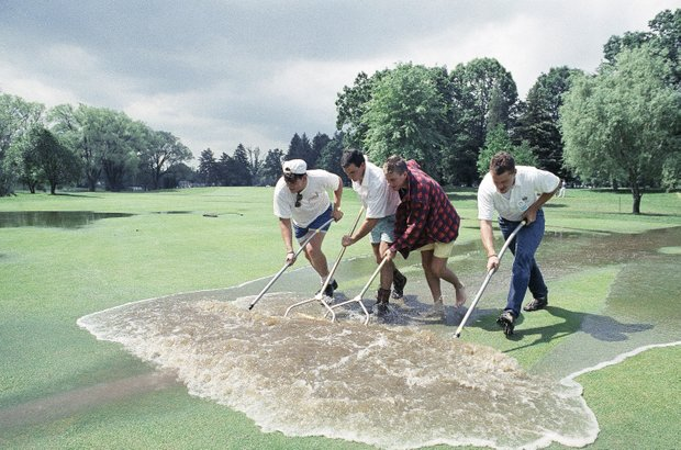 Grounds crewmen squeegee water off the 8th fairway at Oak Hill Country Club in Rochester, New York, Saturday, June 17, 1989, trying to prepare the course for the third round of the U.S. Open.