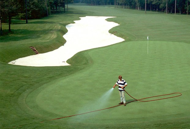 A greenskeeper cools down the green of the 1990 PGA championship on the third hole of Shoal Creek, Birmingham, Ala., July 27, 1990.