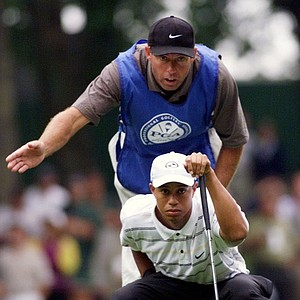 Tiger Woods, of Windermere, Fla., and caddie Steve WIlliams line up a putt on the first green during the first round of the PGA Championship at the Medinah Country Club in Medinah, Ill., on Thursday, Aug. 12, 1999.
