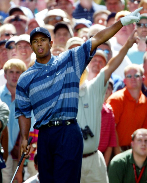 Tiger Woods points left after an errant drive on the 14th hole in the opening round of the PGA Championship Thursday, Aug. 15, 2002 at the Hazeltine National Golf Club in Chaska, Minn.