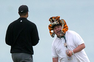 Tiger Woods approaches Nate Lauber, of Fond du Lac, Wis., wearing a tiger hat after Lauber came up from the beach area alongside Whistling Straits in Haven, Wis.,during practice for the PGA Championship on Tuesday, Aug. 10, 2004.