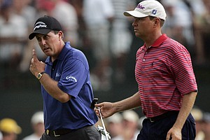 Phil Mickelson, left, walks off the course with Davis Love III during the final round of the 87th PGA Championship at the Baltusrol Golf Club in Springfield, N.J. Sunday, Aug. 14, 2005. Play was suspended until Monday.