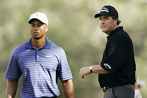 Phil Mickelson, right, looks at Tiger Woods' shot on the 12th fairway during the first round of the PGA Championship golf tournament at Medinah Country Club Thursday, Aug. 17, 2006, in Medinah, Ill.