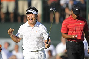 Y.E. Yang of Korea, left, celebrates after making a birdie putt on the 18th green to win the 2009 PGA Championship as Tiger Woods (USA), right, looks down at his ball at Hazeltine National Golf Club on Aug 16, 2009 in Chaska, MN.
