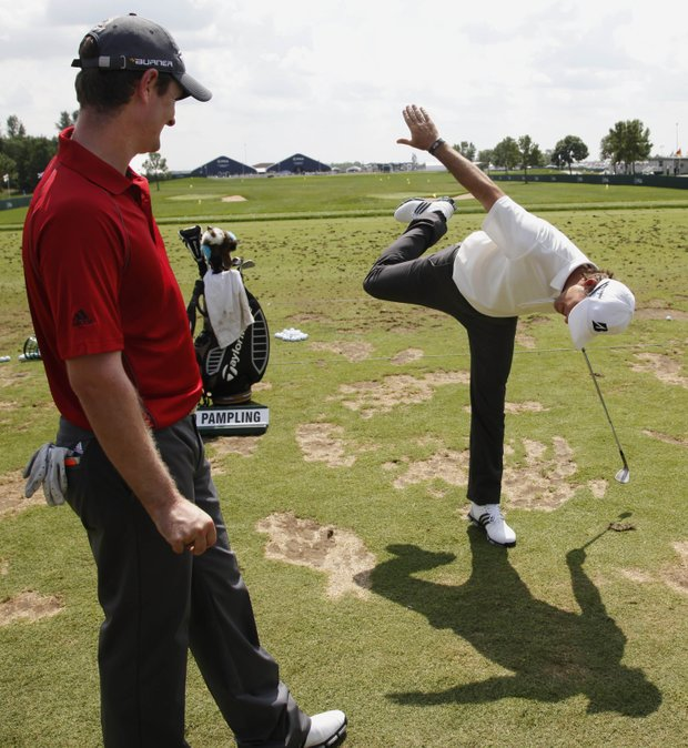 Justin Rose, left, of England, watches as Will MacKenzie gestures at the driving range during a practice round for the 91st PGA Championship at the Hazeltine National Golf Club in Chaska, Minn., Wednesday, Aug. 12, 2009.