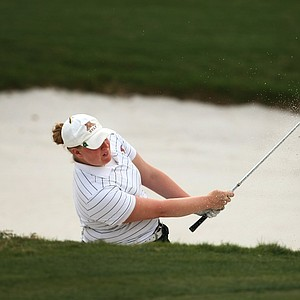 Minnesota's Mary Narzisi hits out of a greenside bunker at No. 18.