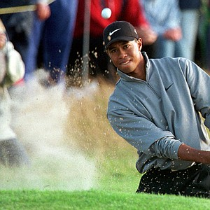 Tiger Woods from the United States blasts out of a bunker aside the 18th green, Friday July 17 1998 at Royal Birkdale Golf Course, in North West England, during the second round of the 1998 Open Golf Championships.