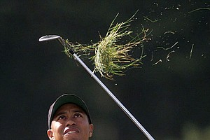 Tiger Woods, of the United States, takes a large clump of grass as he chips onto the 12th green during the first round of the 128th Open Golf Championship at Carnoustie, Scotland, Thursday, July 15, 1999.
