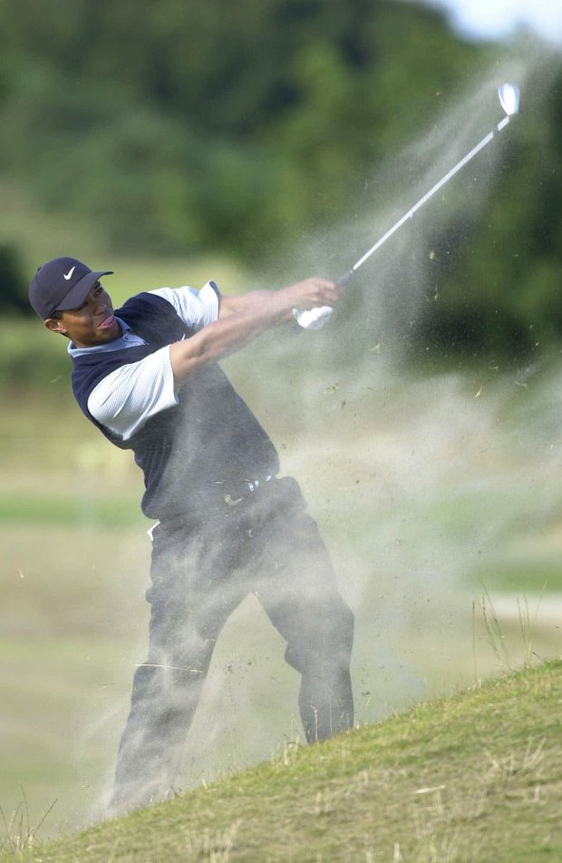 Tiger Woods of the United States sends up a cloud of dust as he plays from the 16th fairway on the third day of the British Open Golf championship on the Old Course at St. Andrews, Scotland Saturday July 22, 2000.