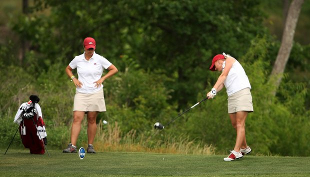 Arkansas' Kelli Shean hits her tee shot at No. 9 as head coach Shuana Estes-Taylor watches during Round 2 of the Women's Division I Golf Championships.