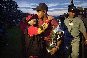 Tiger Woods holds his trophy and embraces his mother, Kultida Woods, left, after winning the U.S. Open Golf Championship at the Black Course of Bethpage State Park in Farmingdale, N.Y., Sunday, June 16, 2002.