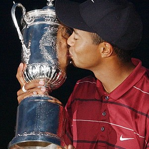 In this June 16, 2002 file photo, Tiger Woods kisses the 2002 U.S. Open Golf Championship trophy after winning at the Black Course of Bethpage State Park in Farmingdale, N.Y. On his web site Friday night, Dec. 11, 2009, Woods announced that he is taking an indefinite break from professional golf.