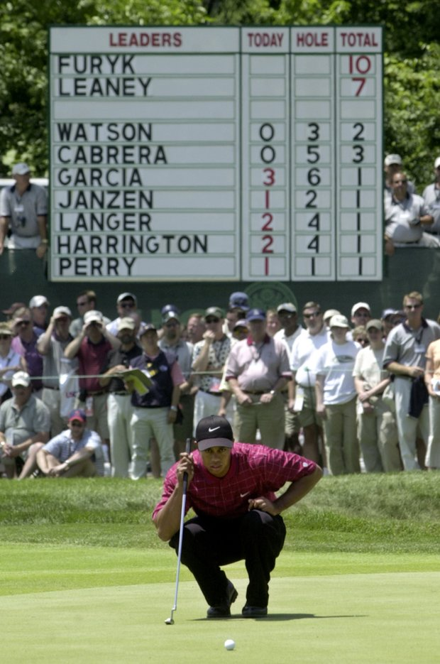 Tiger Woods lines up a birdie putt on the first hole with the leaderboard in the background without his name among the leaders during the final round of the 103rd U.S. Open at the Olympia Fields Country Club on Sunday, June 15, 2003, in Olympia Fields, Ill.