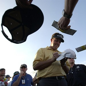 Phil Mickelson, center, signs autographs after the third round of the US Open at Shinnecock Hills Golf Club in Southampton, N.Y., Saturday, June 19, 2004.