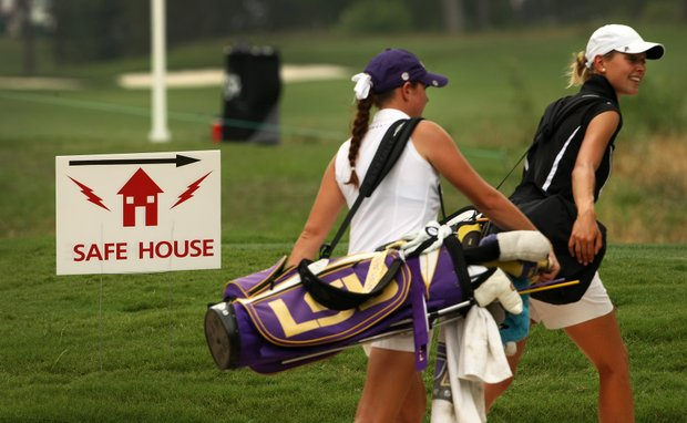 Purdue's Thea Hoffmeister and LSU's Tessa Teachman head to the safe house near the 9th hole after the horns were sounded for a weather delay. Play resumed a little after 5 p.m.
