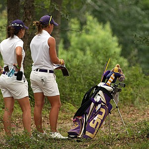 LSU's Austin Ernst, looks over her shot at No. 9, with assistant coach Alex Rather, during Round 3.