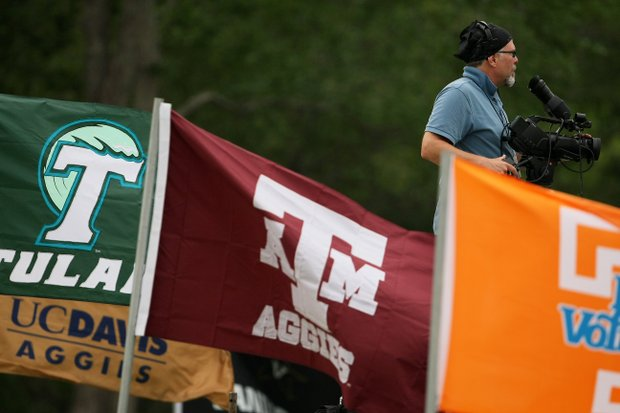 A camera man films the 18th hole amongst school flags during a windy Round 3.