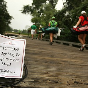 After much rain at the NCAAs a sign warns people to take caution walking across the bridge on the way to No. 9 during the final round.