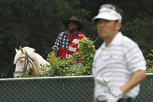 A man on horseback watches from outside the course as Charlie Wi, of South Korea, watches his tee shot on the third hole during the final round of play at the Colonial golf tournament in Fort Worth, Texas, Sunday, May 22, 2011.