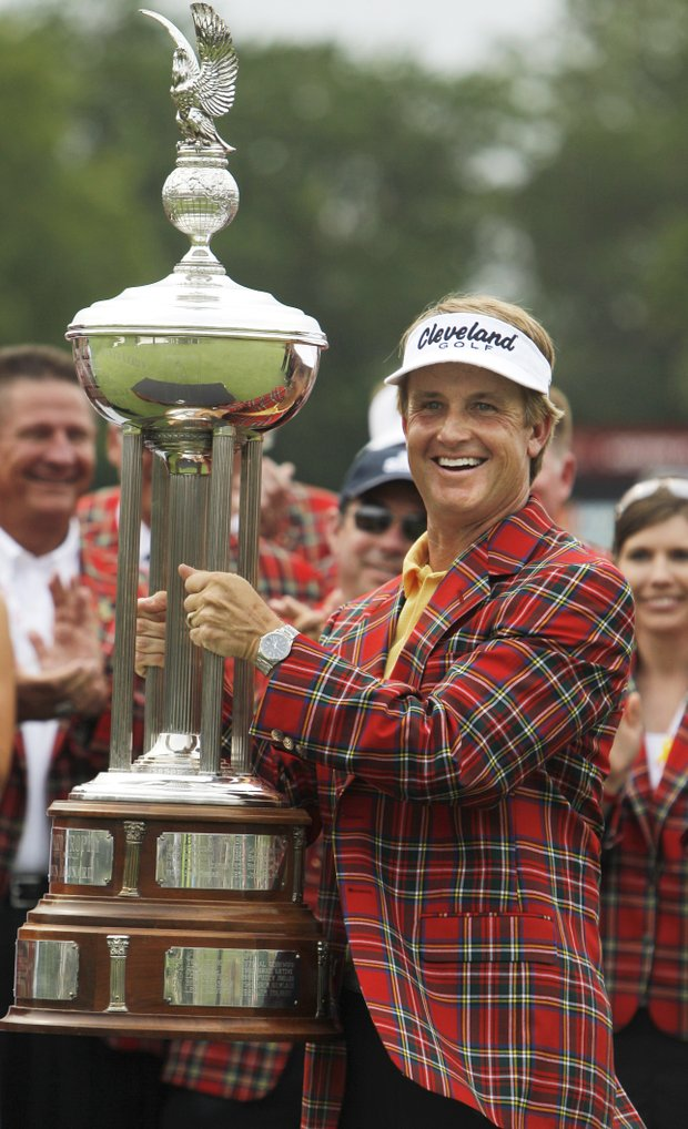 David Toms wears the winner's jacket and holds up the Colonial trophy after winning the golf tournament in Fort Worth, Texas, Sunday, May 22, 2011.