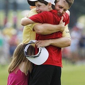 David Toms, right, is hugged by his children Carter, 13, and Pam, 5, after Toms won the Colonial golf tournament in Fort Worth, Texas, Sunday, May 22, 2011.