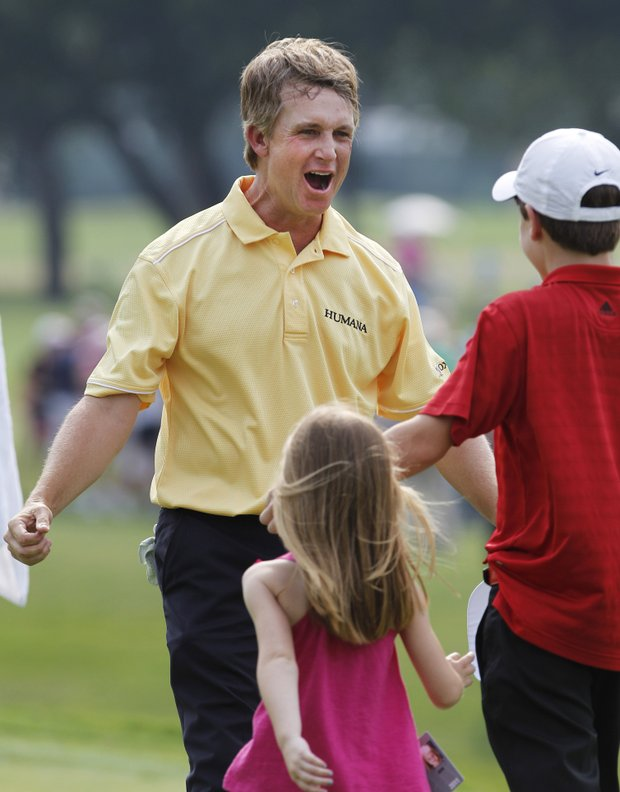 David Toms, left, reacts after winning the Colonial golf tournament as his children Carter, 13, and Anna, 5, run over to him in Fort Worth, Texas, Sunday, May 22, 2011.