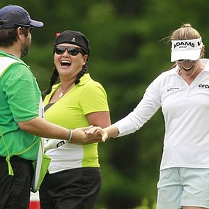 Brittany Lang, right, celebrates with Christina Kim, center, and Kim's caddie Dan Chapman after Lang hit a hole-in-one on the eighth hole during a first round match in the LPGA Sybase Match Play Championship at Hamilton Farm GC, Thursday, May 19, 2011.