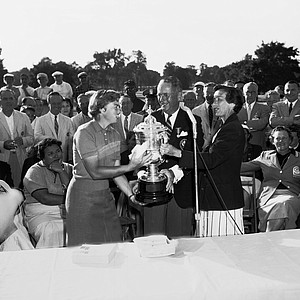 Betsy Rawls, left, of Spartanburg, S.C., receives the Women's National Open Golf Championship Trophy, June 29, 1957. Mrs. Charles Dennehey, right, Chairperson of the Women's Committee of U.S. Golf Association and USGA President Richard S. Tufts, center, presents her with the trophy.