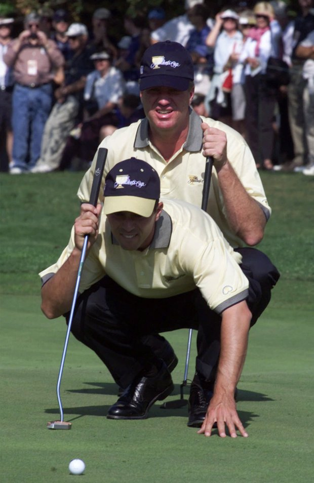 International teammates Mike Weir, of Canada, front, and Steve Elkington, of Australia, line up a putt on the first hole during the fourth round of the President's Cup at the Robert Trent Jones Golf Club in Gainesville, Va., Saturday, Oct. 21, 2000. The team faced the U.S. team of Tom Lehman and Phil Mickelson.
