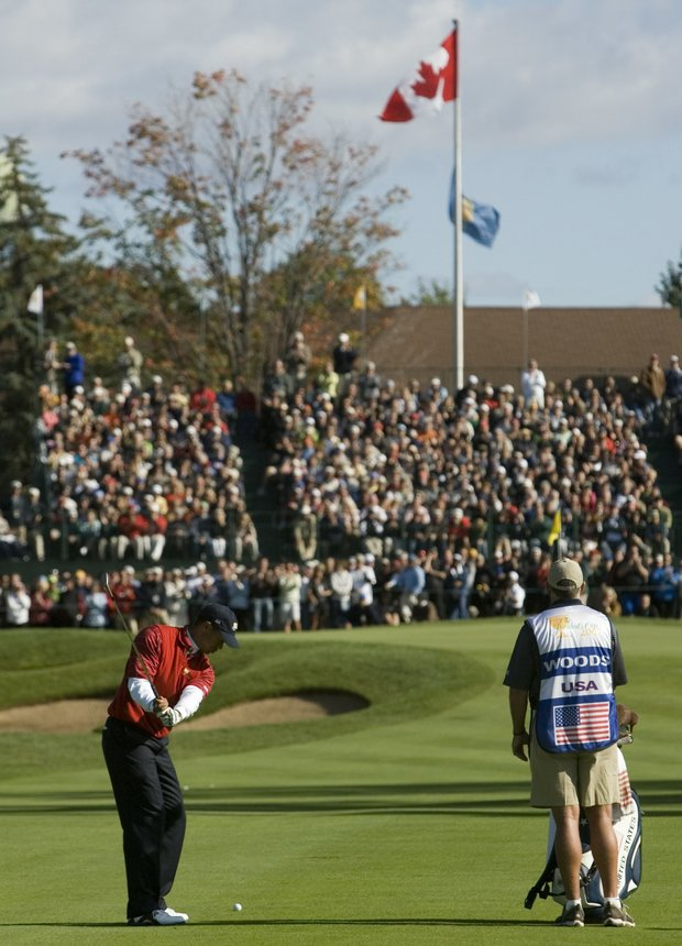United States team member Tiger Woods, lower left, warms up for his approach shot on the ninth hole during fourth round four-ball matches of the Presidents Cup Golf Tournament at the Royal Montreal Golf Club in Montreal, Canada, Saturday Sept. 29, 2007.