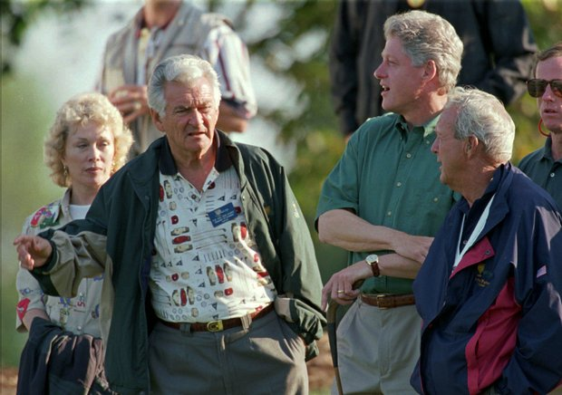 Former Australian Prime Minister Bob Hawke, left, talks with President Clinton and President's Cup team captain Arnold Palmer, right, on the 14th hole during play at the event at the Robert Trent Jones Golf Club in Gainesville, Va., on Friday, Sept. 13, 1996. Hawke's wife Sally is at left.