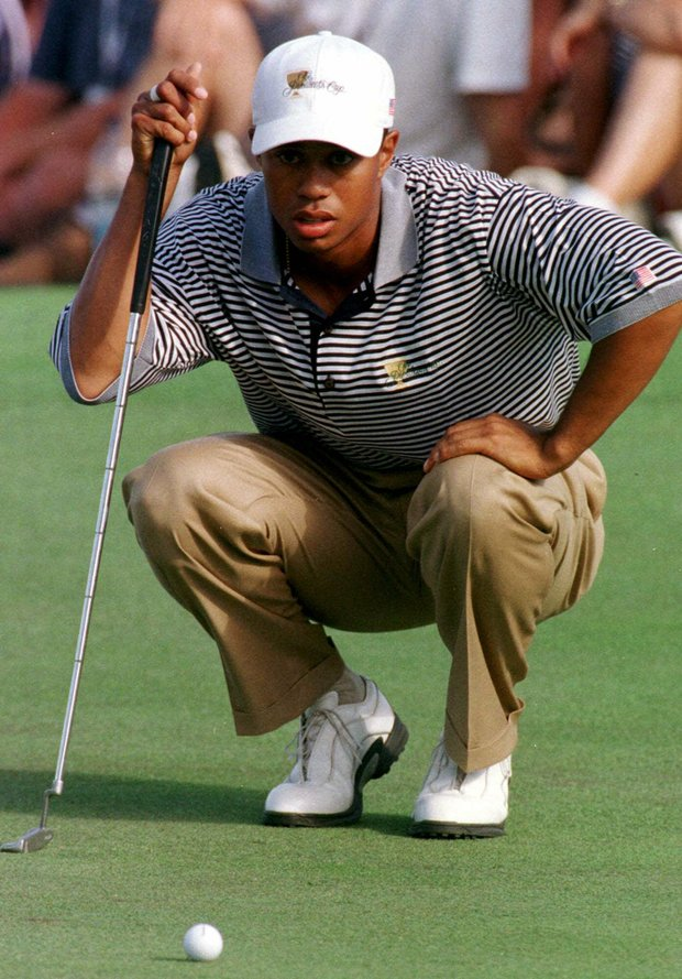 American Presidents Cup golfer Tiger Woods lines up a putt on the third green, during second day morning foursomes with partner Fred Couples against the International team of Craig Parry of Australia and Shigeki Maruyama of Japan at Royal Melbourne Golf Course, Australia, Saturday, Dec. 12, 1998.