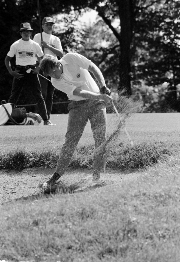 Marvin Giles of Charlottesville, Va., kicks up sand and he blasts toward 9th green yesterday during singles round of Walker Cup Golf tournament in Milwaukee, Wis., August 23, 1969. Giles beat his English team opponent, Charles Green of Dumbarton, Scotland, with a score of one up.