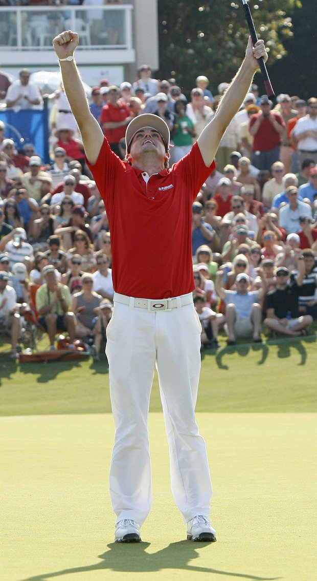Keegan Bradley lifts up his arms after sinking the winning putt on the 18th green of the first playoff hole during the Byron Nelson Championship golf tournament in Irving, Texas, Sunday, May 29, 2011.