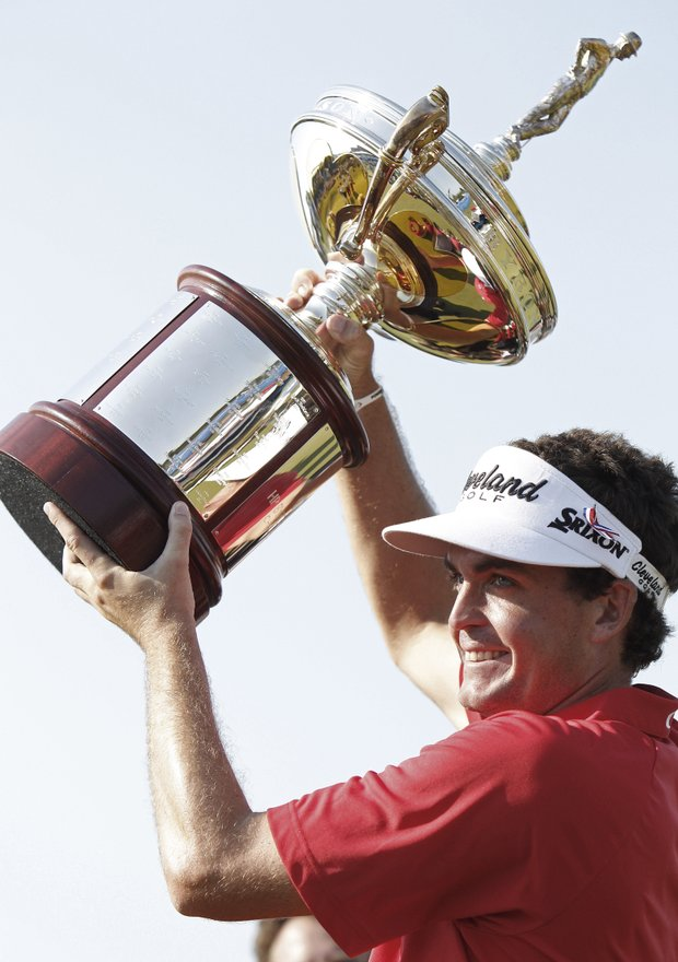 Keegan Bradley holds up the Byron Nelson Championship trophy after winning the golf tournament in Irving, Texas, Sunday, May 29, 2011.