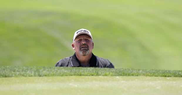 Mark Calcaveccia peers over the top of a trap before hitting out of the sand on the first hole during the final round of the Senior PGA Championship golf tournament at Valhalla Golf Club in Louisville, Ky., Sunday, May 29, 2011.