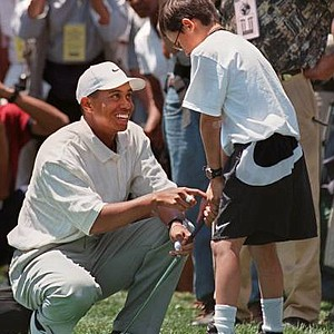 June 15, 1997 - Tiger Woods helps a youngster participating in the Tiger Woods Foundation Junior Golf Clinic Monday, June 16, 1997, on Randall's Island in New York. Thirty of the most talented young golfers from among several hundred had the opportunity to be personally coached by Woods. They were chosen by the National Minority Golf Association and represent 25 community organizations from the New York area.