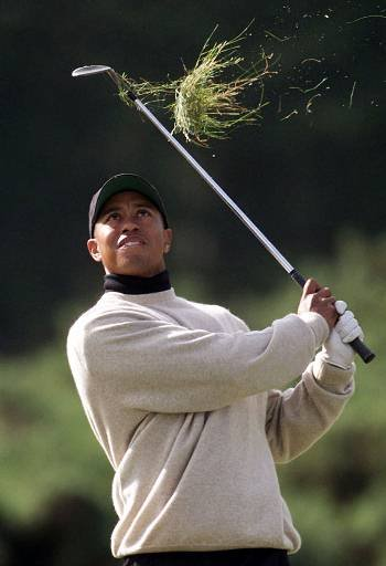 July 4, 1999 - Tiger Woods takes a large clump of grass as he chips onto the 12th green during the first round of the 128th Open Golf Championship at Carnoustie, Scotland, Thursday, July 15, 1999.