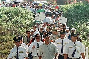 Jan. 11, 1998 - Tiger Woods, center foreground, is surrounded by security as he walks to the first green followed by hundreds of fans during an exhibition game with three other golfers from Asia at the Mimosa Golf and CC at the former U.S. Air Force Base of Clark, 50 miles northwest of Manila, Sunday January 18, 1998. Woods, here for the first time, carded a 71, one under par to win by three strokes against his Filipino rival Felix Casas.