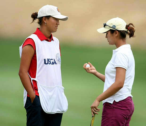 Kimberly Kim talks with her caddie Annie Park during Friday quarterfinal match play of the 61st U. S. Girls' Junior Championship at Trump National Golf Club in Bedminster, New Jersey.
